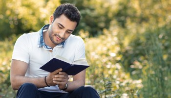Student reading book in a park. Relaxed man holding book, outdoors